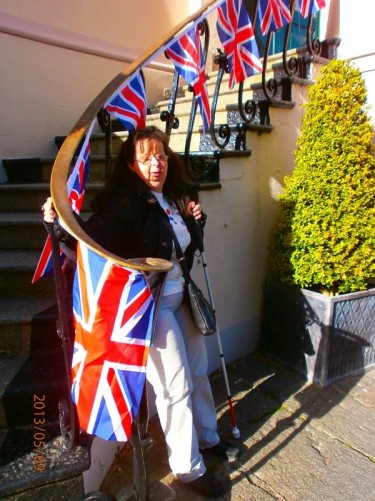 Tatiana at the foot of steps decorated with Union Jacks.