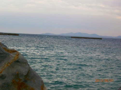 View out to sea. The neighbouring island of Ermoupoli is visible away in the distance.