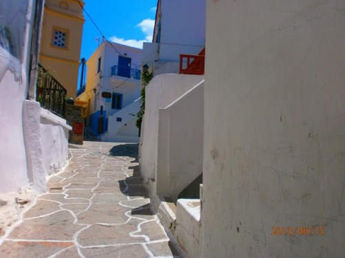 Heading up a pleasant narrow street. A yellow-painted building in front.