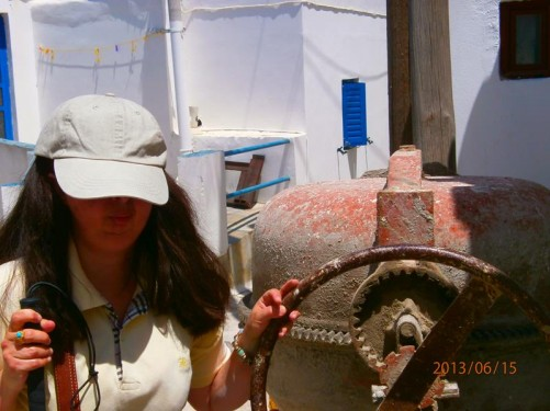 Tatiana standing in a narrow street, touching the metal wheel of a cement mixer.