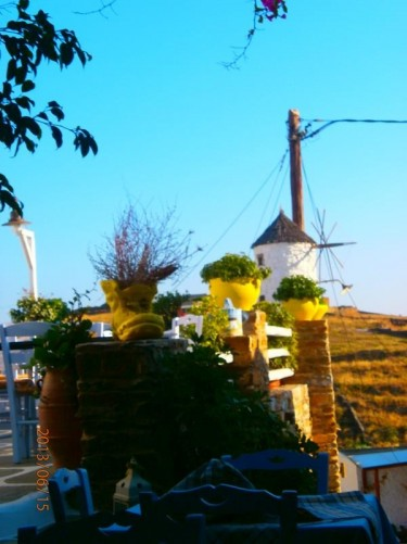 View from a restaurant terrace towards a traditional windmill: cylindrical in shape with white stone walls and a thatched roof.