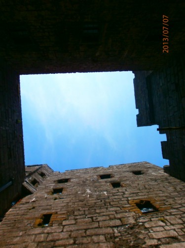 Looking up in the central courtyard of Castle Rushen: high stone walls with crenellated battlements at the top.