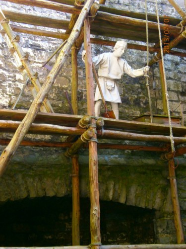 A male manikin holding a rope pulley. He is standing on scaffolding constructed of wood and rope. Perhaps demonstrating historic castle construction methods.