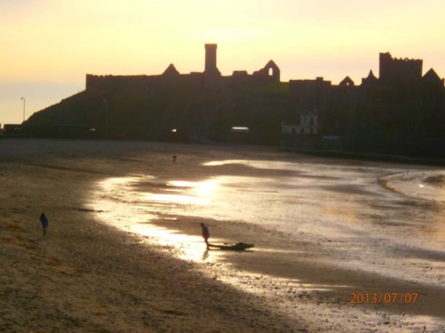 View across the beach in Peel Bay. On the far side, Peel Castle, lit by the setting sun.