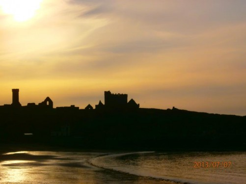 Sunset over Peel Castle. The castle a silhouette beneath the sky lit in shades of yellow and orange.