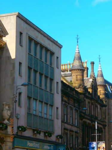 Looking along High Street towards a Victorian building with decorative turrets on its roof. The upper floors house the Highlander Backpackers Hostel.