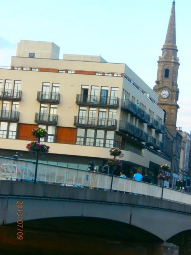 View over the Ness Bridge and up along Bridge Street. At the junction of Bridge Street and Church Street is a clock tower topped with a spire. This is known as The Steeple (or Tollbooth Steeple) and dates from 1791.