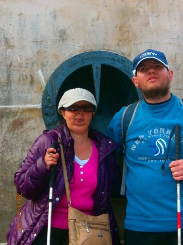 Tatiana and Tony at the foot of the Mercat Cross. A metal sundial can be seen embedded into the stone behind.