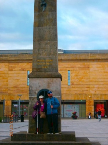 Tony and Tatiana in Falcon Square. They are at the foot of the Mercat Cross. A granite and sandstone plinth topped with a bronze unicorn. It is 12 metres (40 feet) high. There are also four bronze Peregrine Falcons attached to the sides.