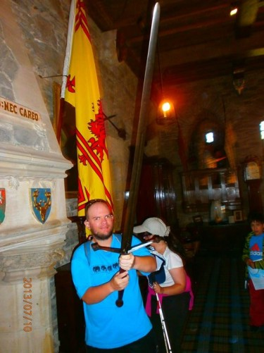 Tony next to a fireplace inside the castle holding a large sword (claymore).