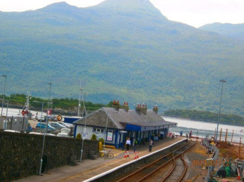 The railway station at Kyle of Lochalsh with the tracks stopping almost at the water's edge. The channel of water in front separates mainland Scotland from the Isle of Skye. A good view of the mountains rising up on the Isle of Skye in front.