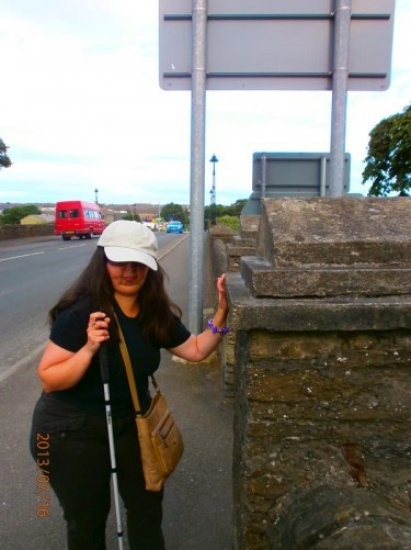 Tatiana standing at one end of a road bridge over the Thurso River at the edge of the town.