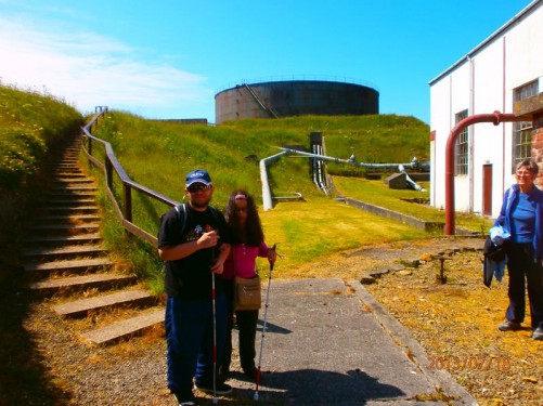 Tony and Tatiana outside the museum. A single storey building to the side and the old oil storage tank behind. Various old pipes running from the buildings across the grass.