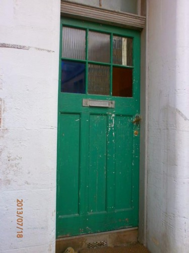 A weathered-looking door to a house.