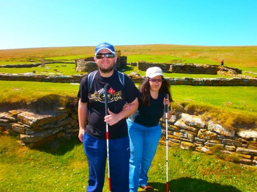 Tony and Tatiana with stone walls behind. Also, beyond, the exposed grassy landscape of the island.