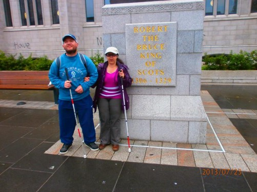 Tony and Tatiana at the foot of a large statue of Robert the Bruce on horseback. The inscription on the base reads: 'Robert the Bruce, King of Scots, 1306-1329'. Located outside Marischal College on Broad Street.