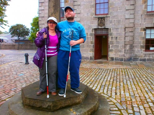Tony and Tatiana standing in front of a mercat cross (head late medieval, shaft more recent). The building behind is the Old Town House dating from the late 18th century. Located at the top of the High Street.