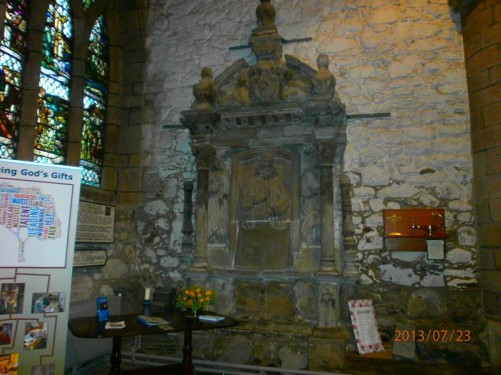 A stone altar inside the church. A stained-glass window to the left.