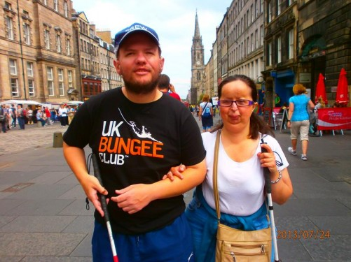 Close up of Tatiana and Tony on the Royal Mile. The steeple of St Giles' Cathedral can be seen behind them.