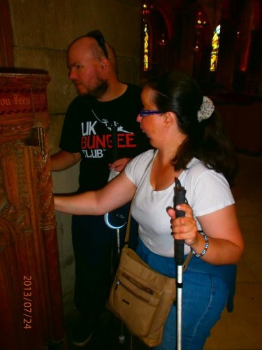 Tony and Tatiana touching a wooden carved object, possibly part of a tomb, inside St Giles' Cathedral. The present church dates from the late 14th century, though it was extensively restored in the 19th century.