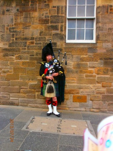 A man playing the bagpipes in traditional Scottish piper's uniform, including a feather bonnet and kilt.