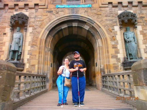 Tatiana and Tony in front of the Gatehouse, standing on a wooden bridge over a ditch. Statues in alcoves on either side: William Wallace (right) and Robert the Bruce (left). The gatehouse was built in 1886-8 for aesthetic rather than defensive reasons.