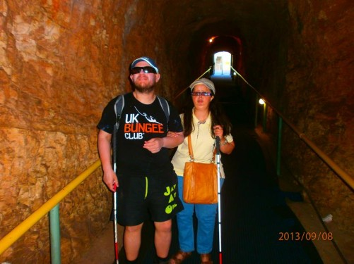 Tony and Tatiana in a tunnel cut through rock that leads to Melissani Cave. The cave contains a subterranean lake. The rock above part of the lake has collapsed revealing the sky above.