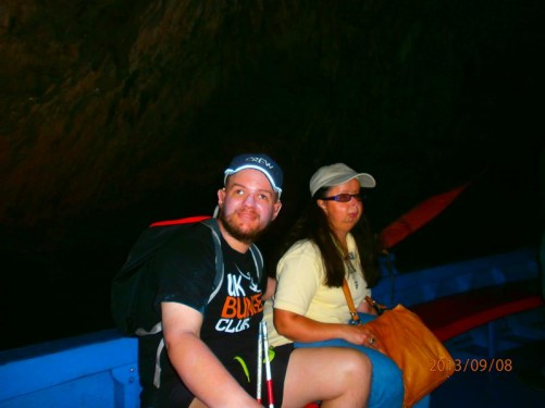 Still in the boat, now in semi-darkness, the rock wall of the cave just visible behind.