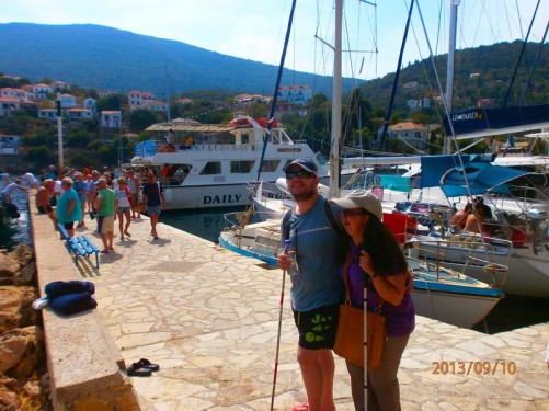 Tony and Tatiana on the harbour side in the small coastal village of Kioni on Ithaki. Lots of people leaving the cruise boat off to the side.