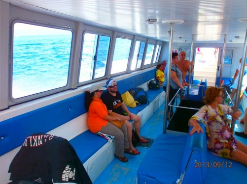 Tatiana and Tony with other passengers inside a boat. The boat left from a small harbour in Zakynthos and headed south along the island's coast.