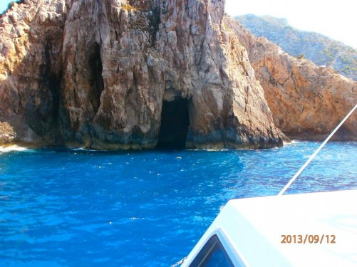 "Now back on the boat looking at the entrance to a sea cave in a cliff. There are several ""Blue Caves"" cut into cliffs around Cape Skinari on Zakynthos's north coast."
