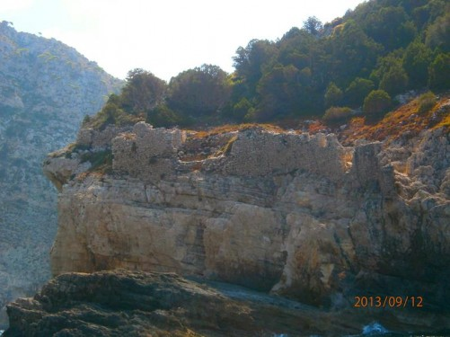 Ruins of stone walls high up on the edge of the cliff. Appears to have once been a building.