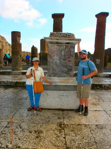 Tony and Tatiana touching a marble plinth. Probably the base to a statue.