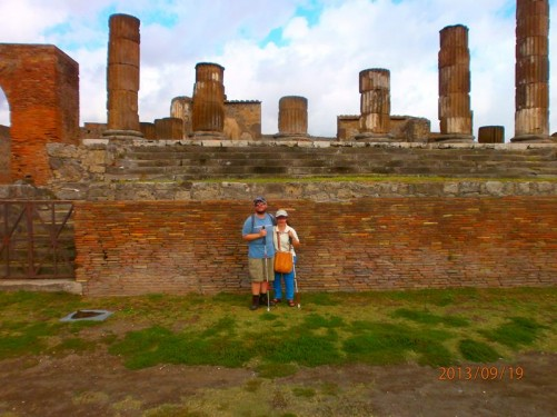 Tatiana and Tony in front of an ancient brick wall. Up above are a row of columns, again part of the Temple of Jupiter.
