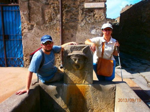 Tatiana, Tony behind a Roman street fountain, once connected to an aqueduct. On top is an upright stone slab with a person's face carved on the front. Water would have once come out of the mouth.