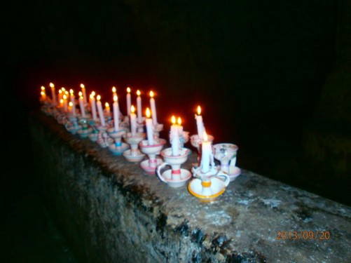 A group of lit candles in pottery holders, left on an underground wall. These candles are carried by visitors.
