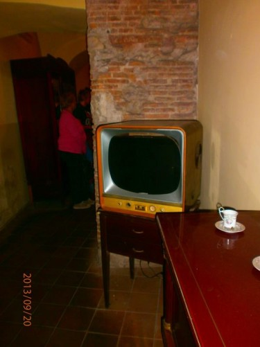 An old television, probably dating from around World War Two, with other furniture, in an underground room.
