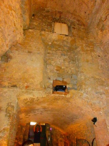 Another room that appears to be partially underground. Daylight can be seen from the top of steps in front. A stone built wall and ceiling above.