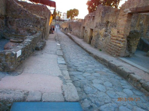 View along an ancient street. The ruins of houses on either side standing to first floor level.