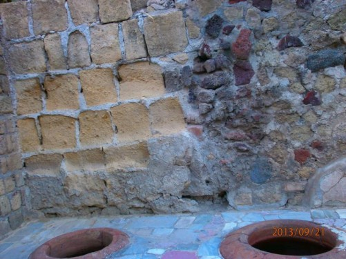 A pair of round holes on a flat surface. Perhaps a thermopolium with the holes used to hold amphorae (pottery containers used to transport wine and other liquid or dry goods).