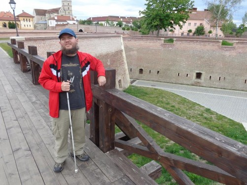 Tony on a wooden foot bridge leading over stone ramparts on the edge of the citadel.