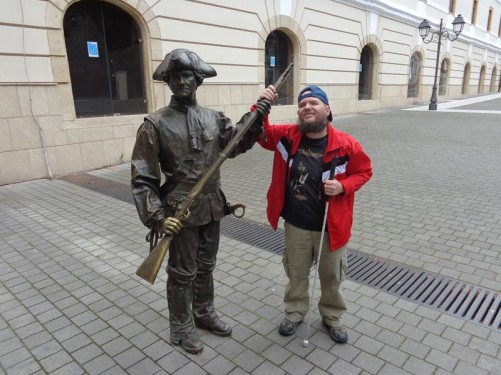 Tony touching a bronze statue of a soldier or guard with his musket held aloft.