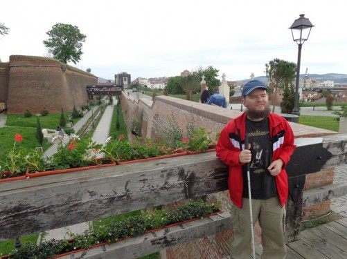 Tony on the bridge to one of the gates. Behind are two tall rampart walls built of brick with a broad ditch or moat in between them. The moat is landscaped with grass and has footpaths running along it.