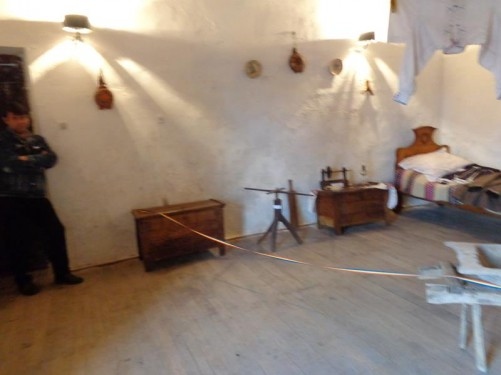 Museum display of an historic bedroom, including a wooden bed and two chests of draws.
