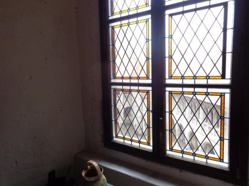 Looking at a leaded window through which the inner courtyard can be seen.