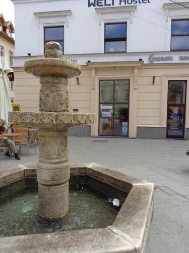 A compact fountain with a decorative stone column at its centre. Strada Nicolae Bălcescu.