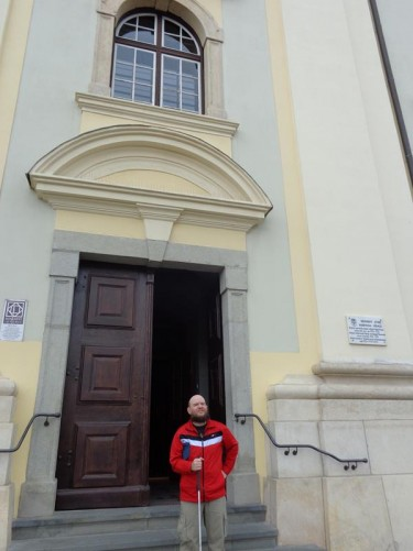 Tony outside the main entrance to the Roman Catholic Church on the north side of Grand Square. It is baroque in style and was built between 1726 and 1738. It is painted cream with a red tiled roof. There's a clock tower at the west side (not in view).