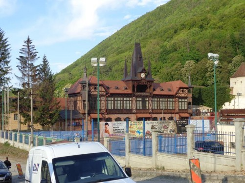 Tennis courts with a large partly gothic looking building behind. The building has tall pointy towers on its roof. It was built in 1894, entirely out of wood. It is part of the Olimpia Tennis Club and houses a restaurant.