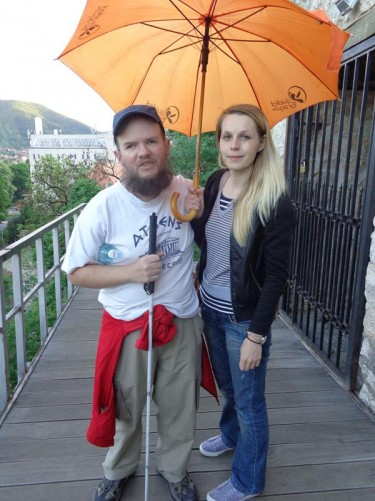 Tony with the female walking tour guide in front of the Black Tower (Turnul Negru). She is holding an umbrella.