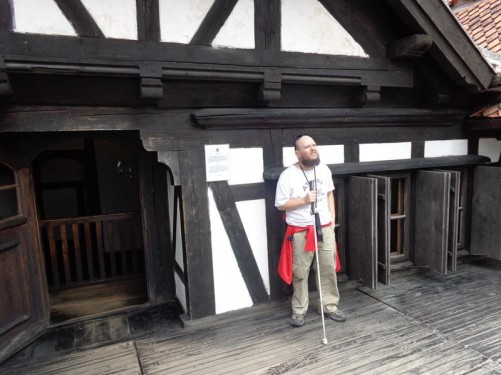 Tony standing on a wooden rooftop balcony at Bran Castle.